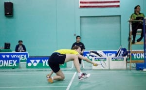Badminton player lunges for shuttle and is on her knees.